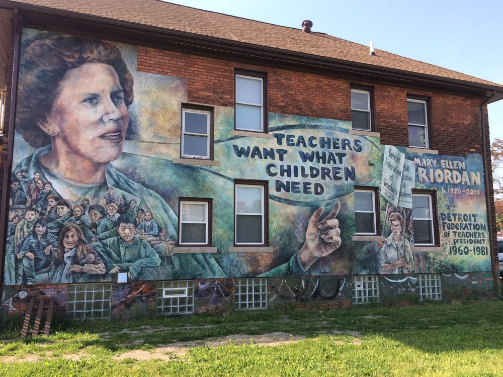 A building with a mural on the side of it. The mural depicts a woman and these words are written in the mural: Teachers want what children need, Mary Ellen Riordan.