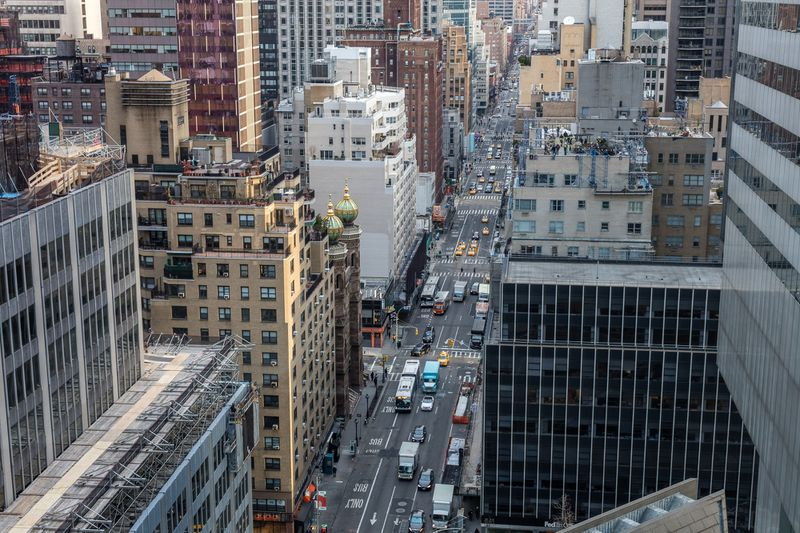 An aerial view of a large roadway in a city, with cars, trucks, and buses on the street.