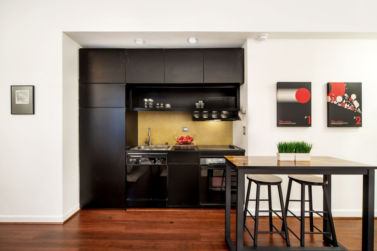 A kitchen with hardwood floors, black cabinetry, and a tall wooden table with two chairs.