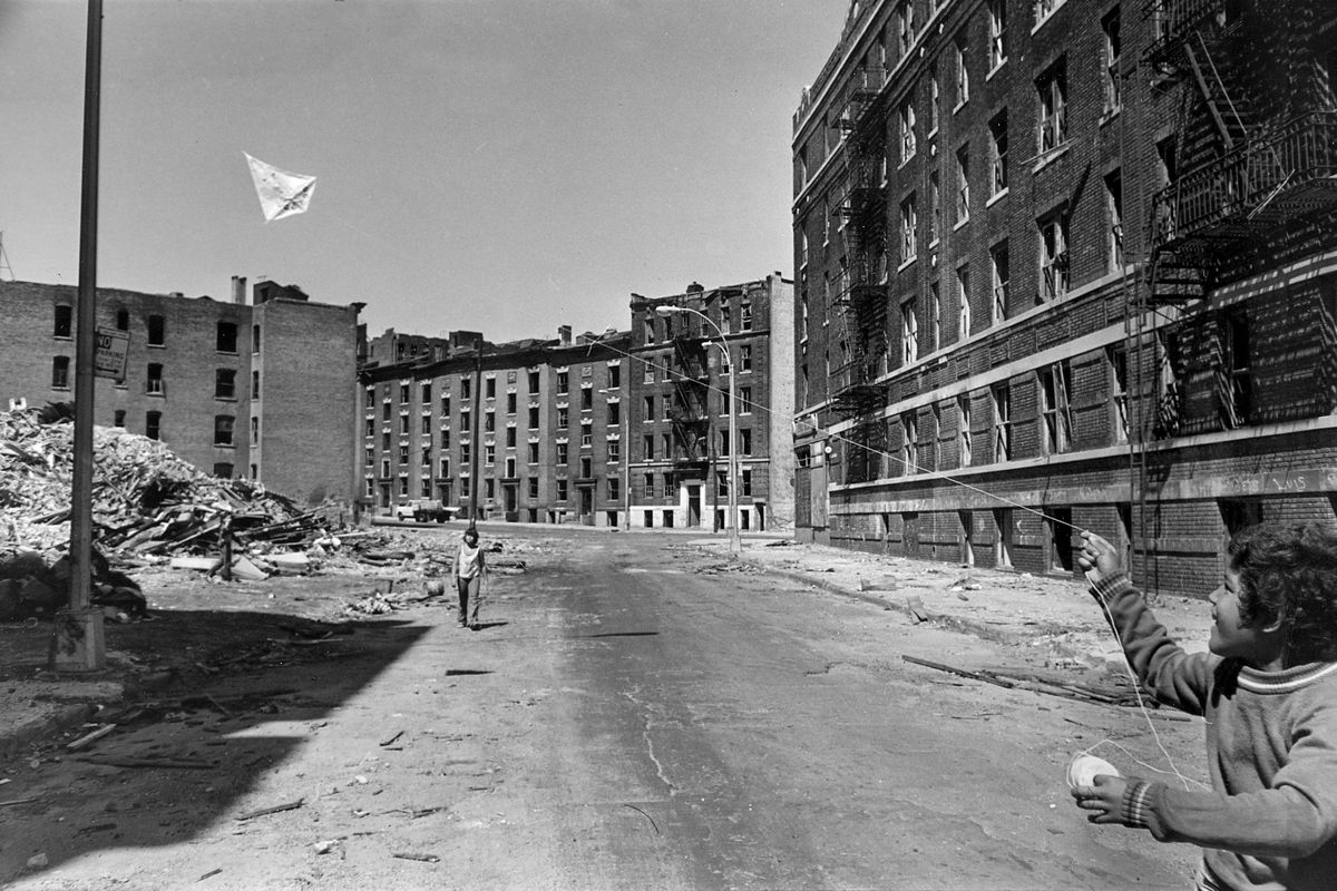 bbf7736c1a42 Youths fly a kite in a street bordered with firegutted buildings in the  South Bronx section of New York City in June