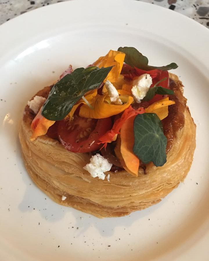 A thick pastry topped with tomatoes and herbs