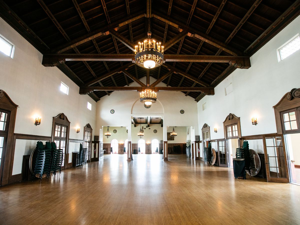 The interior of the Detroit Yacht Club. There is a hardwood floor, painted white walls, and the ceiling has exposed wooden beams. Chandeliers hang from the ceiling.