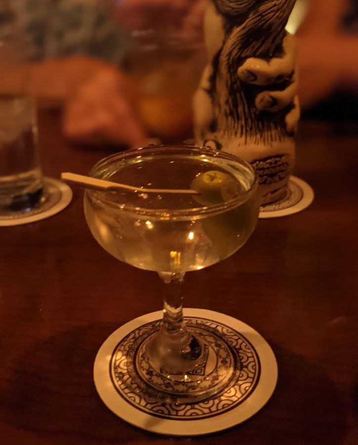 Martini on a coaster with a tiki cup in the background