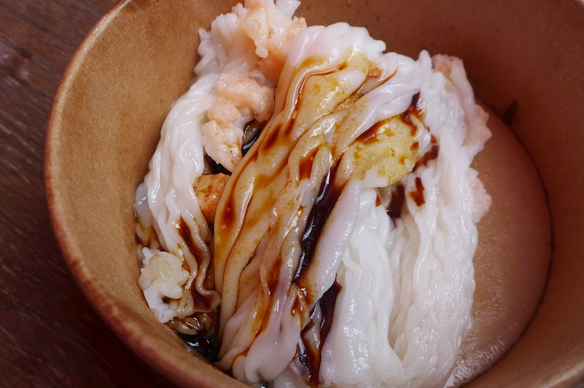 A round cardboard container with wobbly white noodle rolls with a shrimp seen here and there.