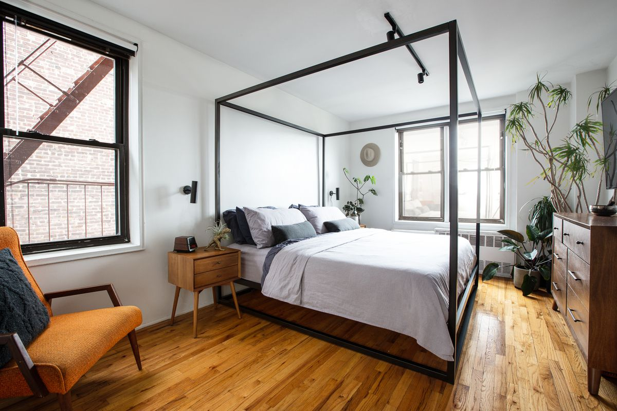 A bedroom with hardwood floors, a large bed, several planters, and wooden furniture.