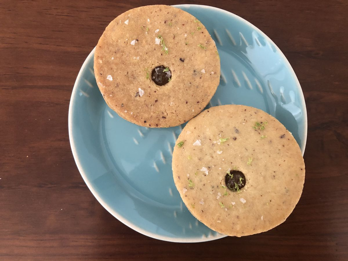 Two golden brown pineapple linzer cookies with sprinkles of sea salt flakes and lime zest on top placed on a blue plate