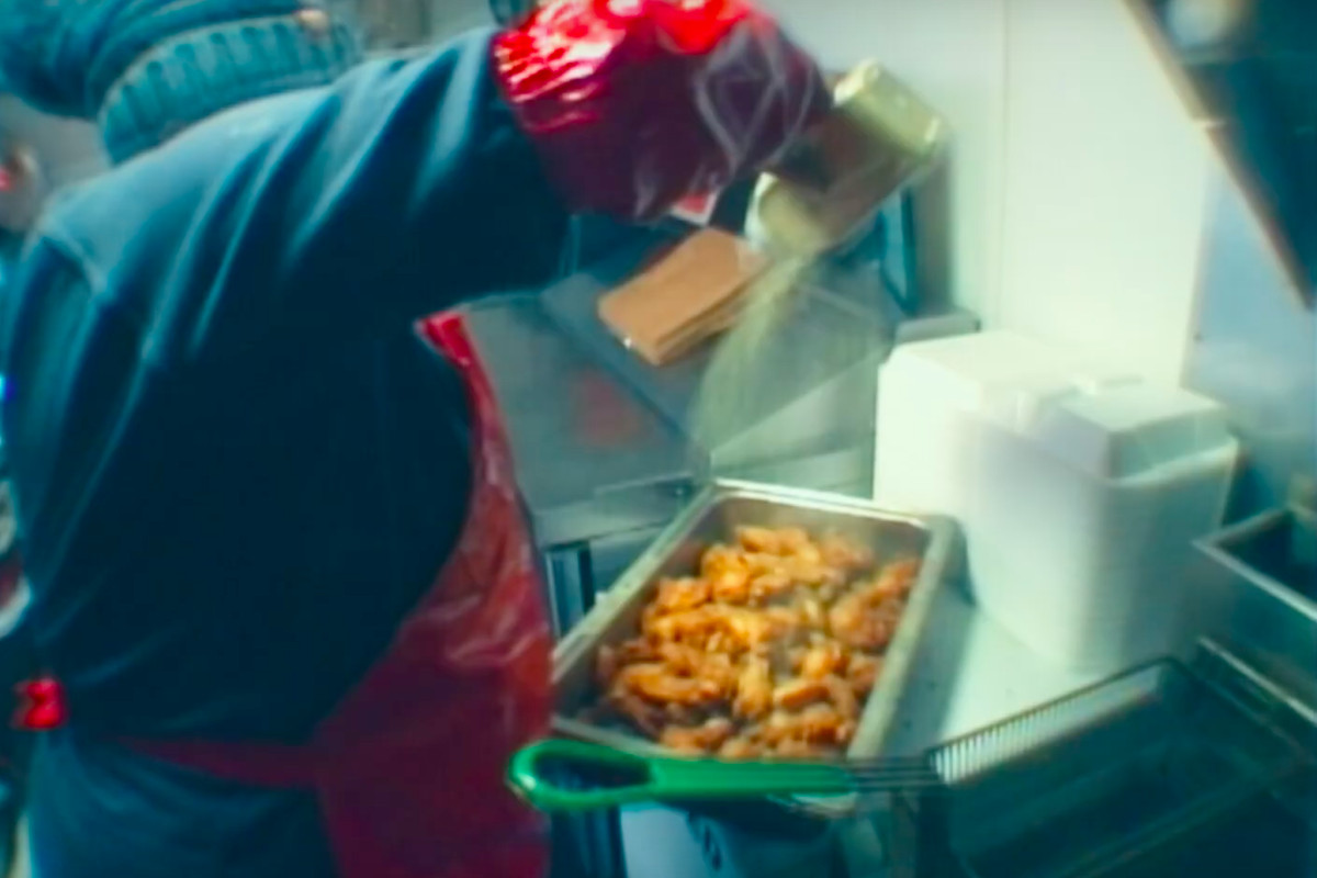 A woman in a red apron seasons a big tray of chicken wings in Aminé's new video
