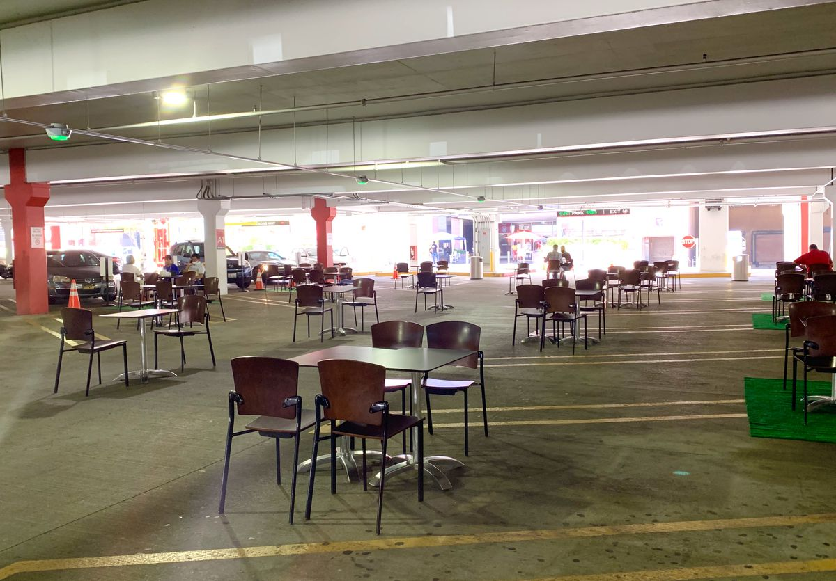 A parking garage is filled with chairs and tables clustered into dining areas as part of a mall's program to give people places to safely eat outdoors during the coronavirus pandemic.