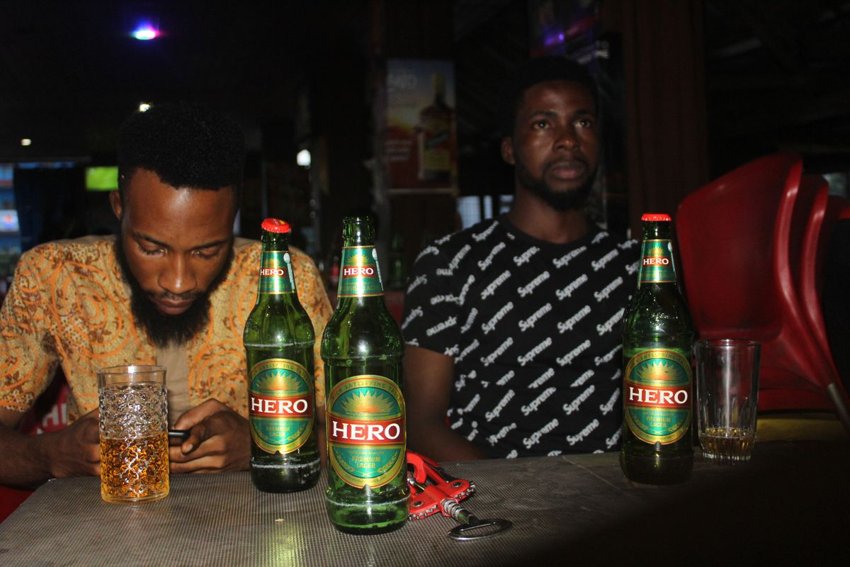 Two men sit behind a table. On the table are two glasses and three bottles of Hero Lager.