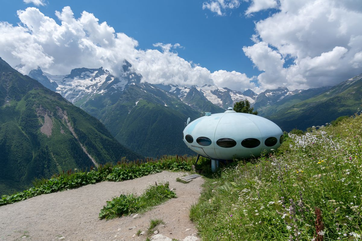 A Futuro House in Russia. The house is shaped like a spaceship with oval windows. It is perched on a cliff. In the distance are mountains.