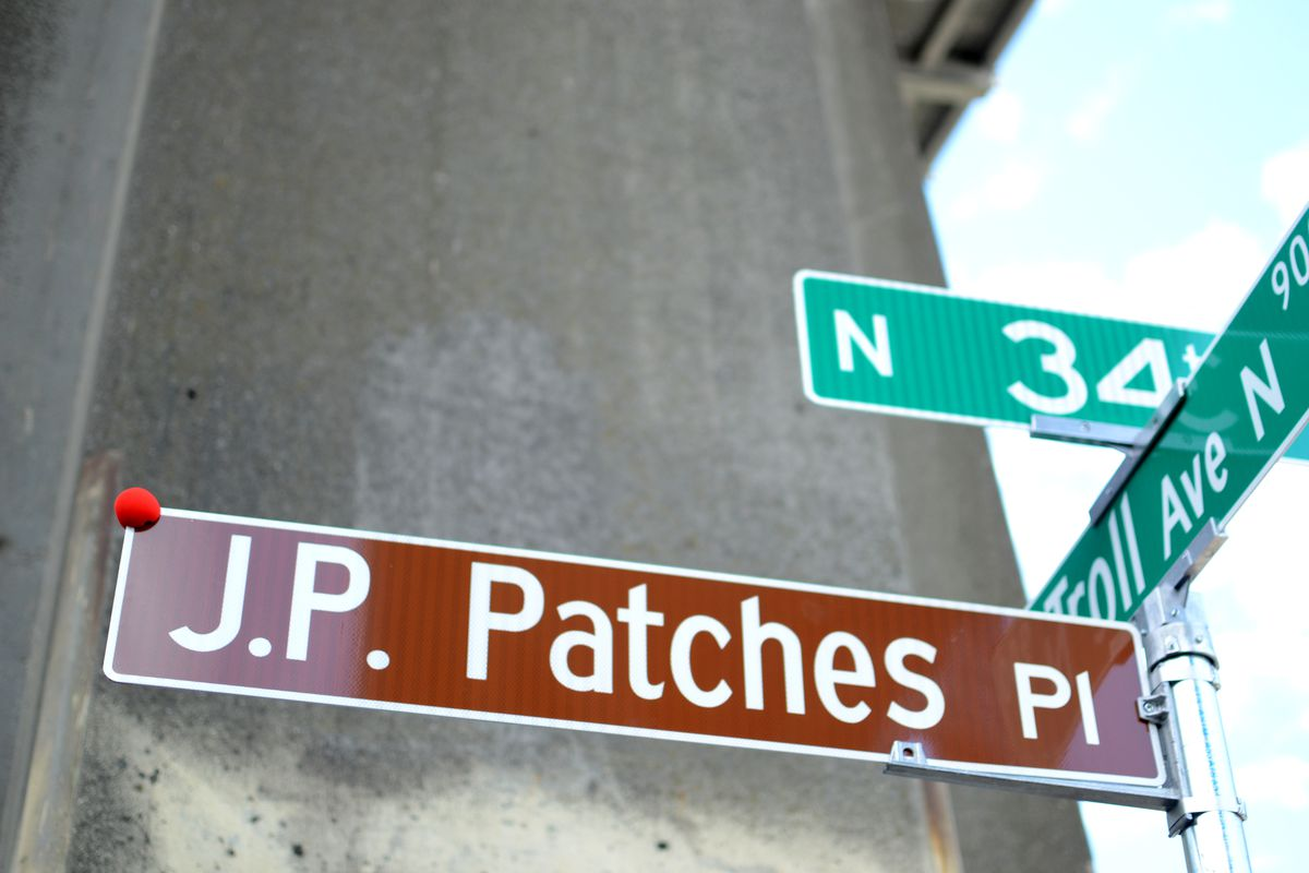 """A close-up of a street marker with three directional street signs. On top, a left-to-right green sign reads """"N 34th.""""  Below, another green sign front-to-back reads """"Troll Ave N."""" Below, a brown left-to-right sign reads """"J.P. Patches Pl."""""""