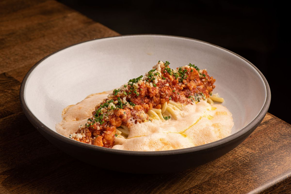 A lobster bolognese with light foam in a bowl.
