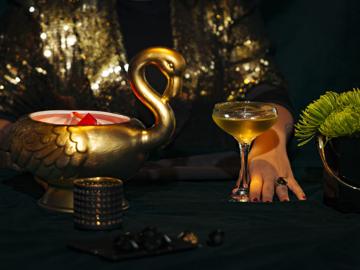 A gold swan on a dark table, with a hand pushing forward a coup glass filled with a cocktail