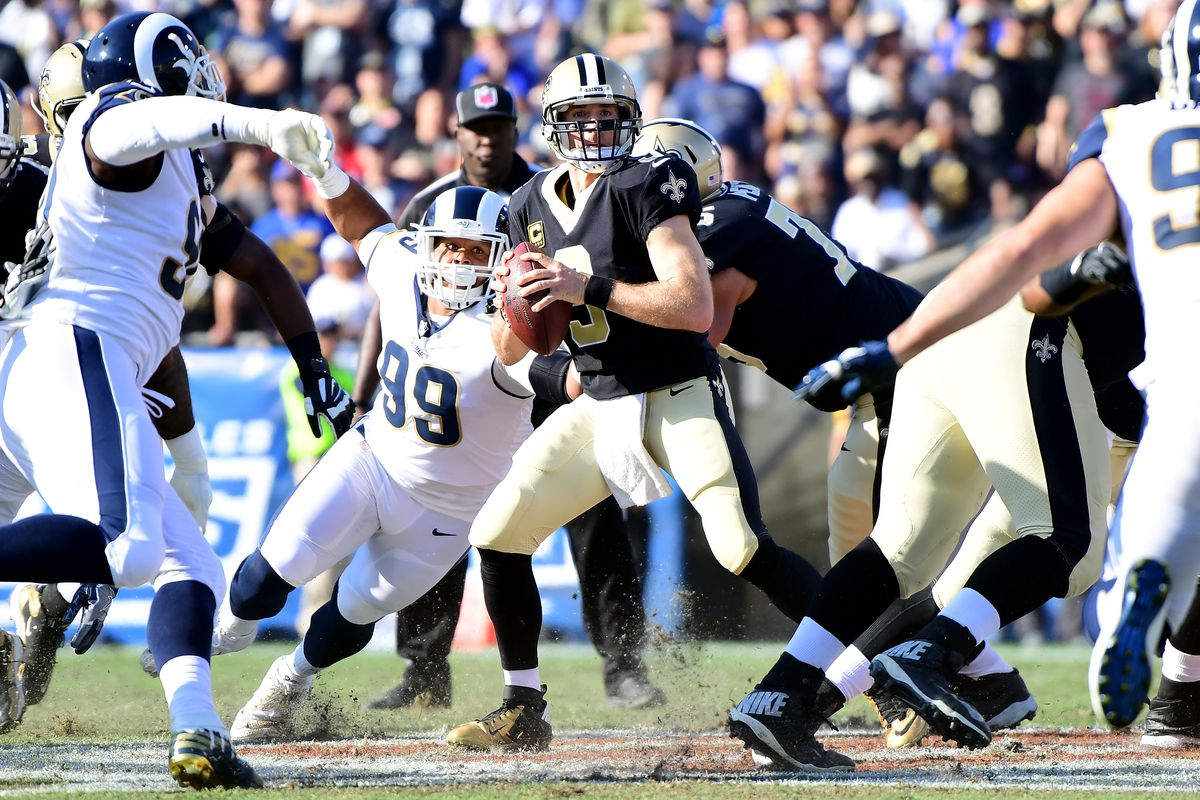 LOS ANGELES, CA: New Orleans Saints quarterback Drew Brees (9) looks to throw from a collapsing pocket against the Los Angeles Rams defense at the Los Angeles Memorial Coliseum.