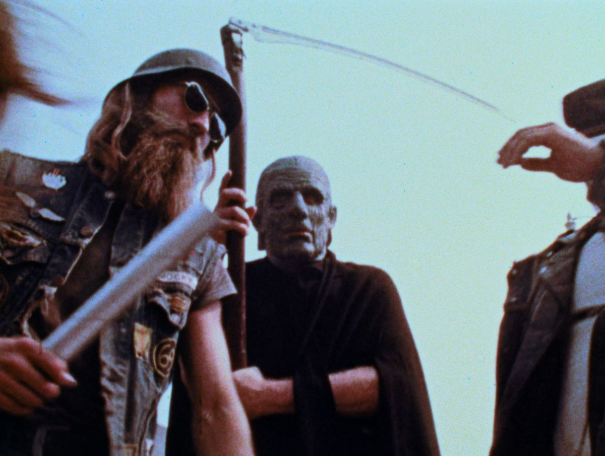 A thuggish-looking biker-type wielding what looks suspiciously like a silver paper-towel tube and a bald man in black with a scythe looking like the Grim Reaper in George A. Romero's The Amusement Park