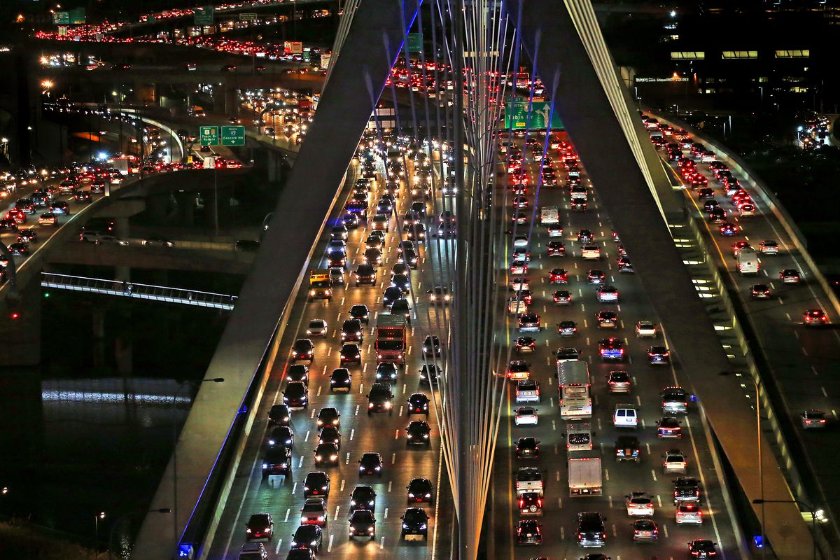 Aerial view of dense city traffic at night, with cars stuck on a bridge.