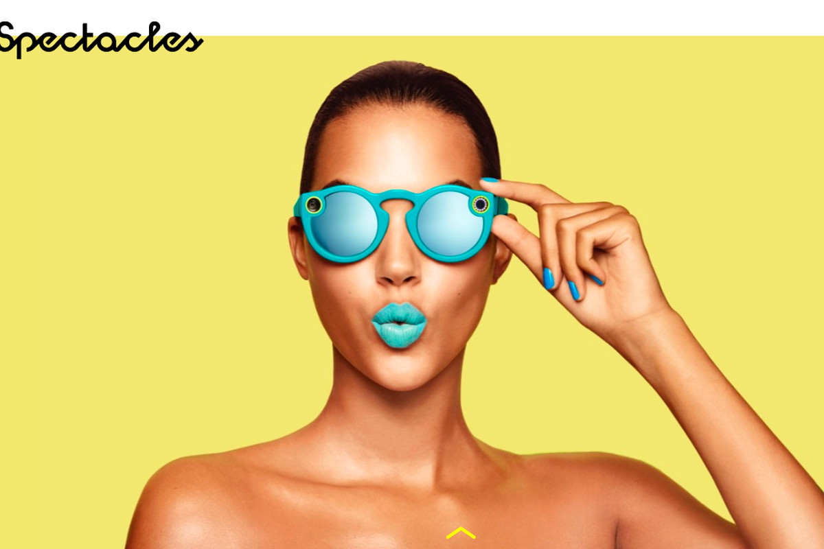A woman wearing aqua Snap Spectacles and matching aqua lipstick and aqua nail polish