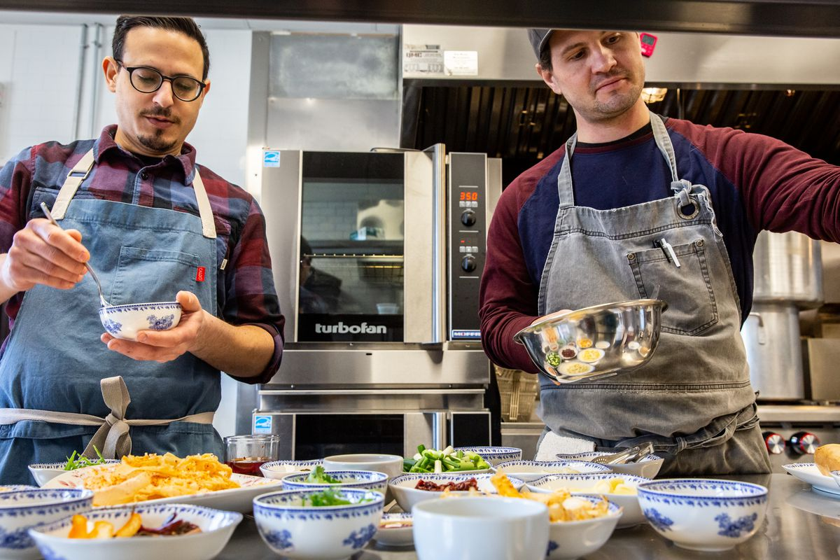 Two chefs with aprons in a kitchen in front of a variety of ingredients.