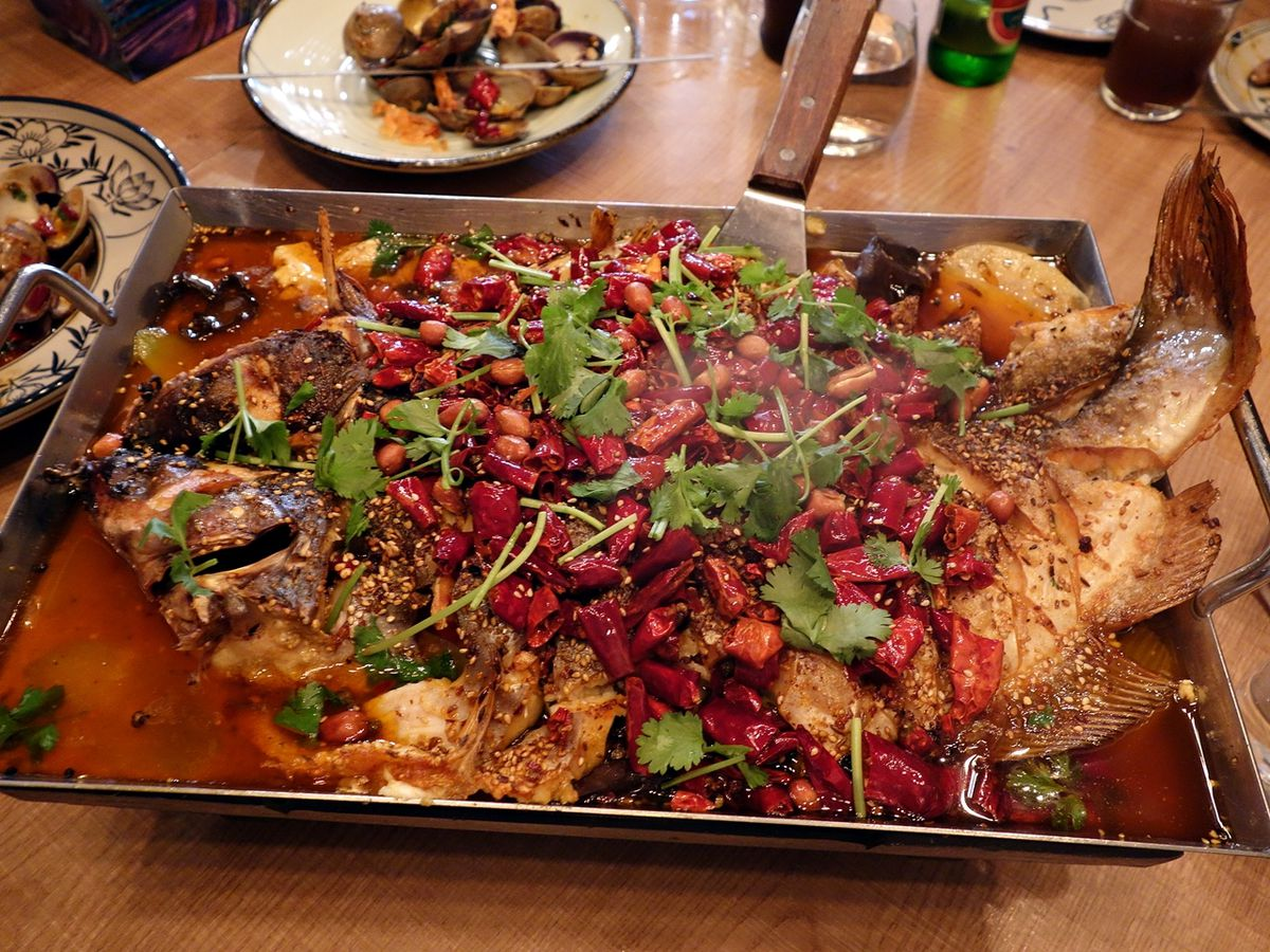 A metal tray with a whole roasted fish buried beneath a pile of chiles, herbs, peanuts, and seeds with other dishes visible on the table around the periphery.