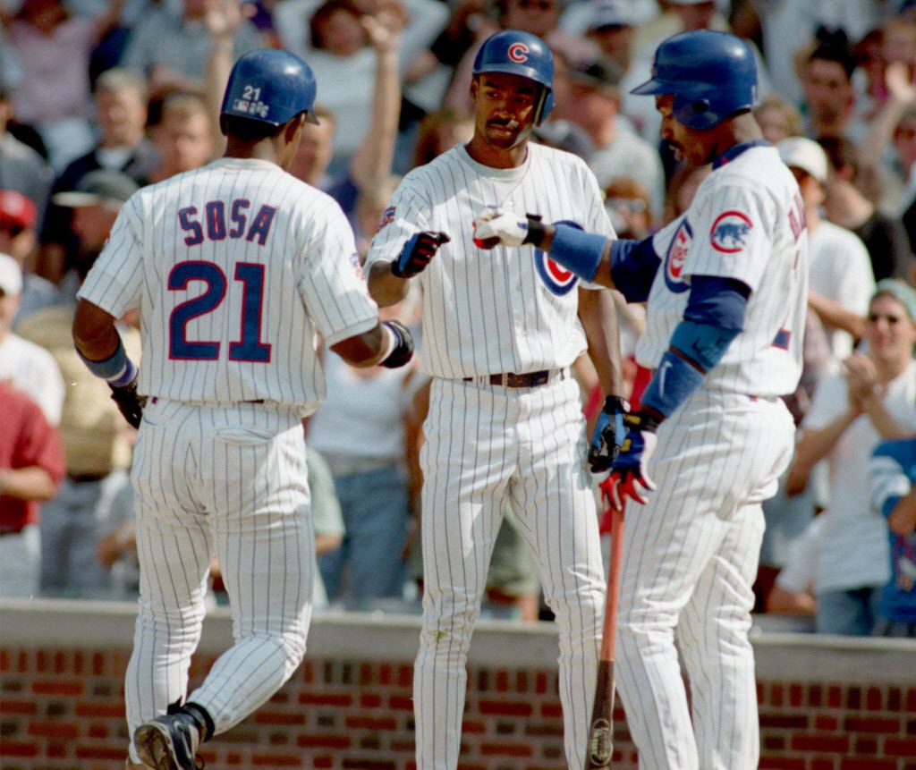 Chicago Cubs' Doug Glanville, center, and Shawon Dunston, right, congratulate Sammy Sosa (21) after hittinga home run in the eighth inning Sunday, Aug. 24, 1997, in Chicago. Sosa's home run help defeat the Expos 12-3. (AP Photo/Michael Conroy)