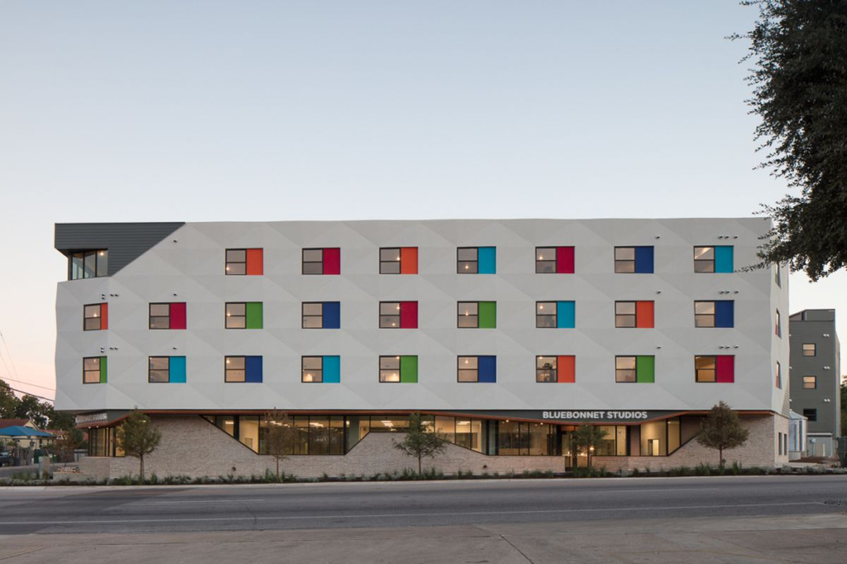 Four-story building with white facade punctuated by rows of colorful windows, ground floor picture windows