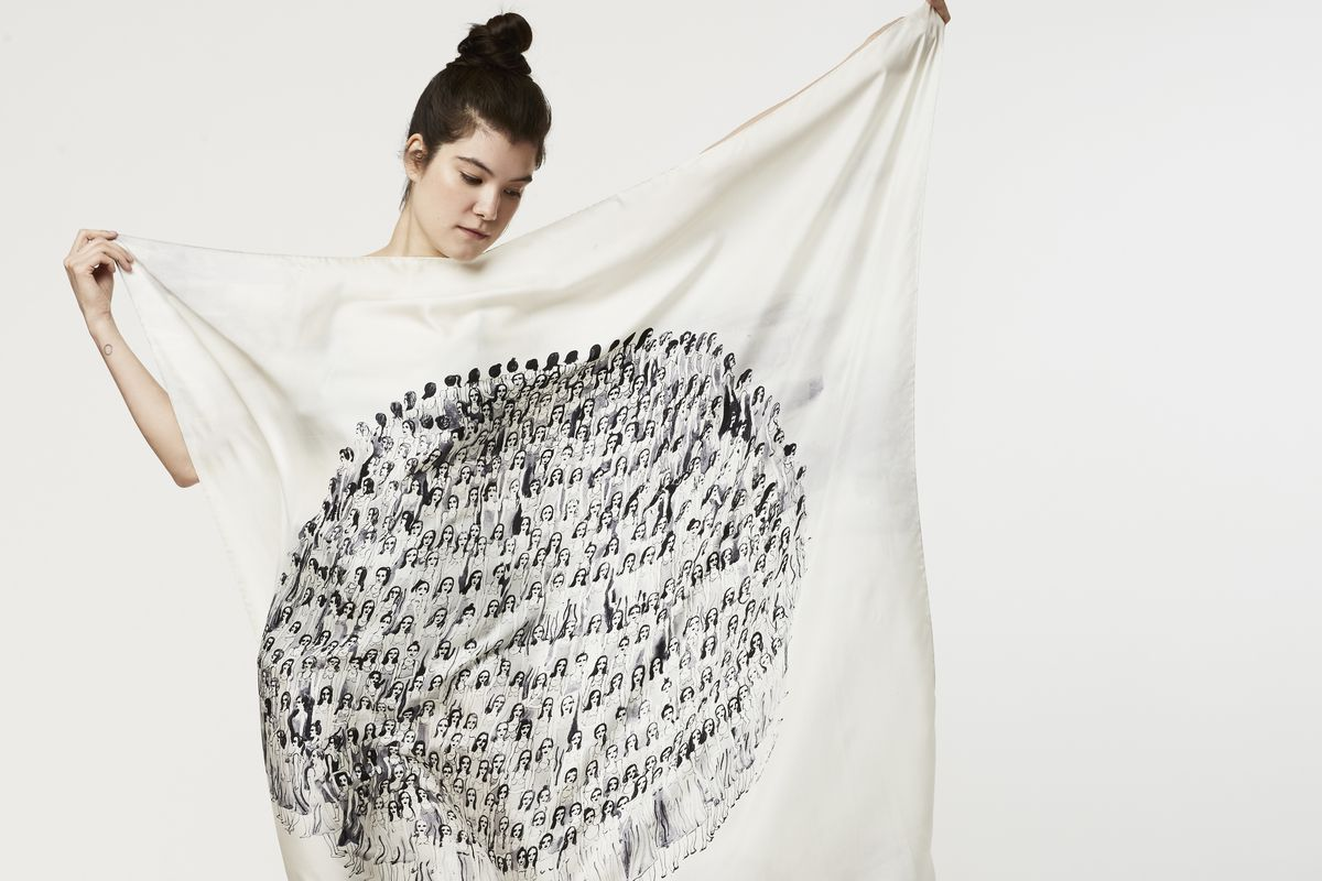 A woman holding a white silk scarf with a drawing of several women standing in a circle