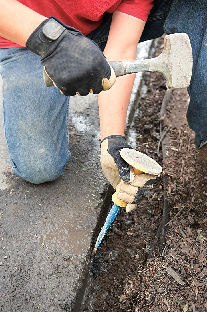 Man Cleans Up And Back-Cuts Rough Edges With Brick Set And Maul For Driveway Edging