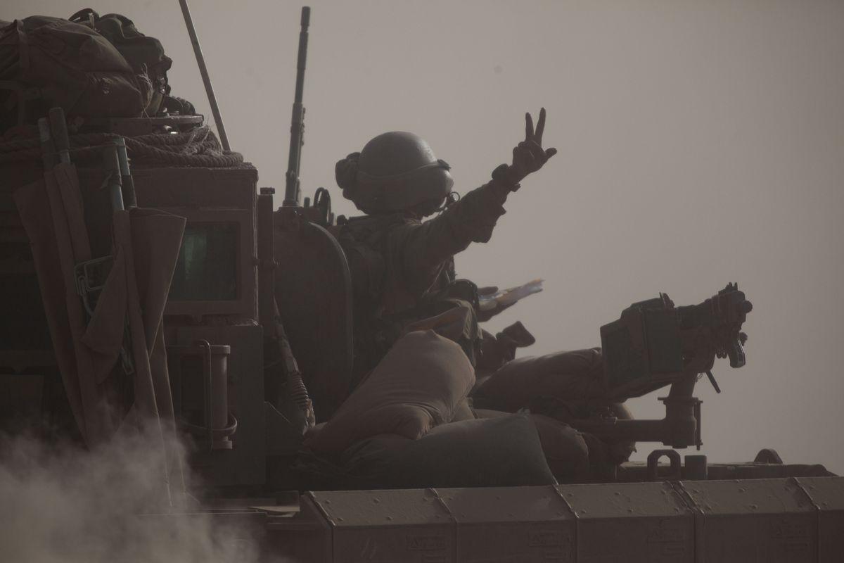 An Israeli soldier rides a tank near the Gaza border