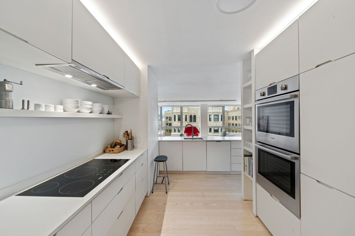 A gallery style-kitchen with modern white cabinets, integrated metal appliances, and hardwood floors.