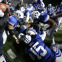 BYU tight end Andrew George (88) is on the bottom of the pile celebrating with teammates after scoring the winning touchdown in overtime as BYU defeated Utah 26-23 at LaVell Edwards Stadium in Provo Saturday.