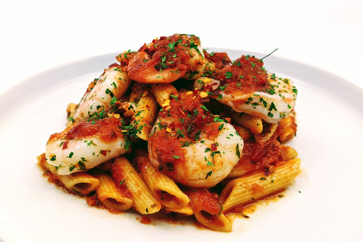 A white plate with red sauce pasta and shrimp.