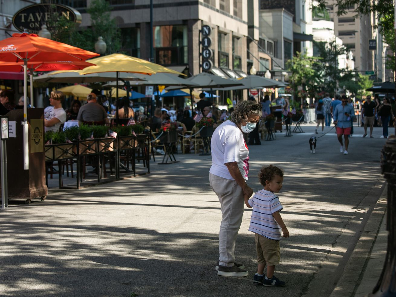 A woman and child pass by Tavern on Rush, where dozens of diners crowded the street. Many say they're eager to go to bars and restaurants again now that COVID-19 restrictions in Chicago and statewide have been lifted.