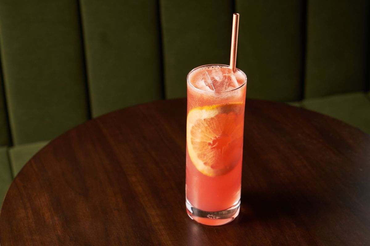 A pinkish drink with a white straw and submerged slice of orange.