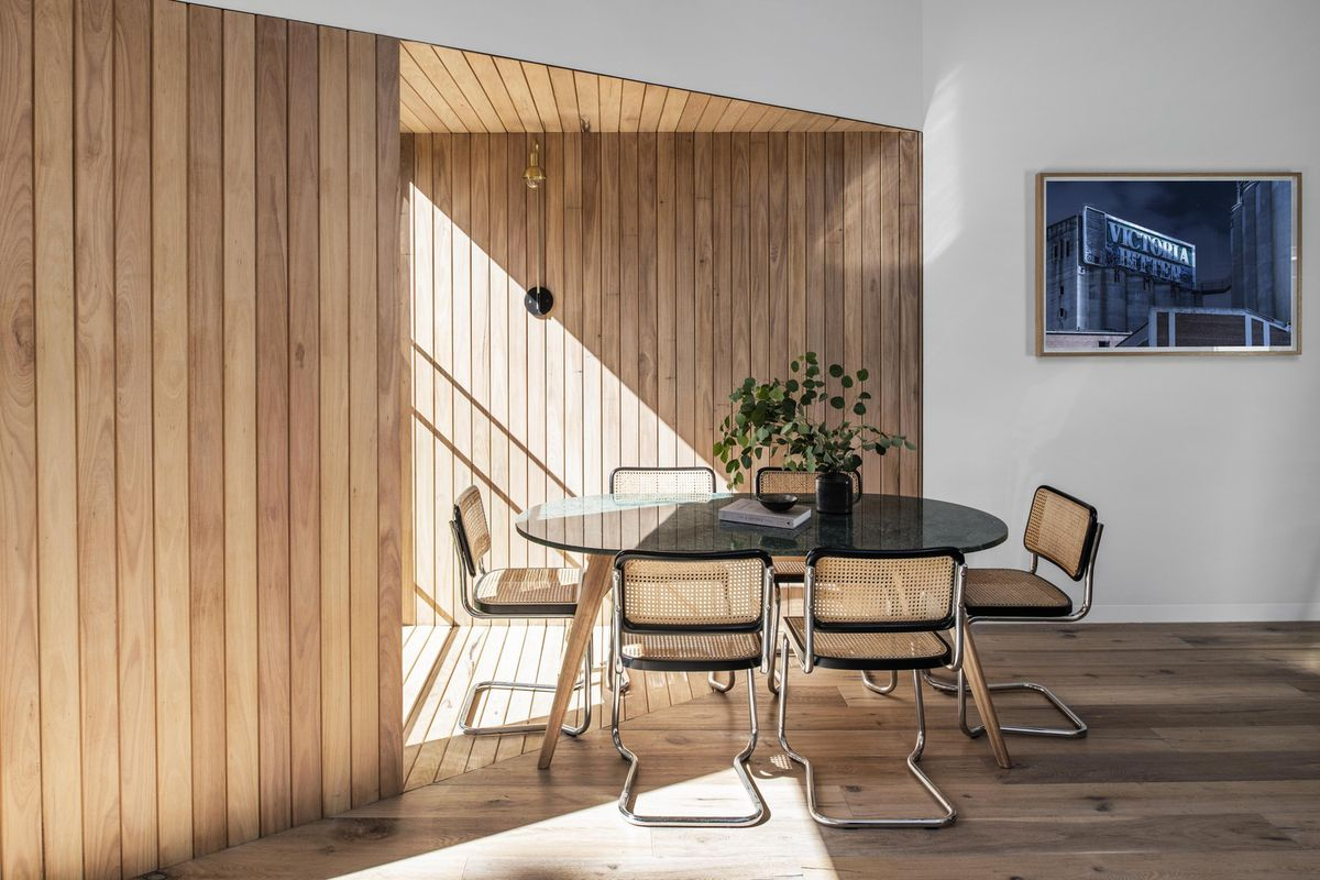Wood-clad dining nook with glass table.