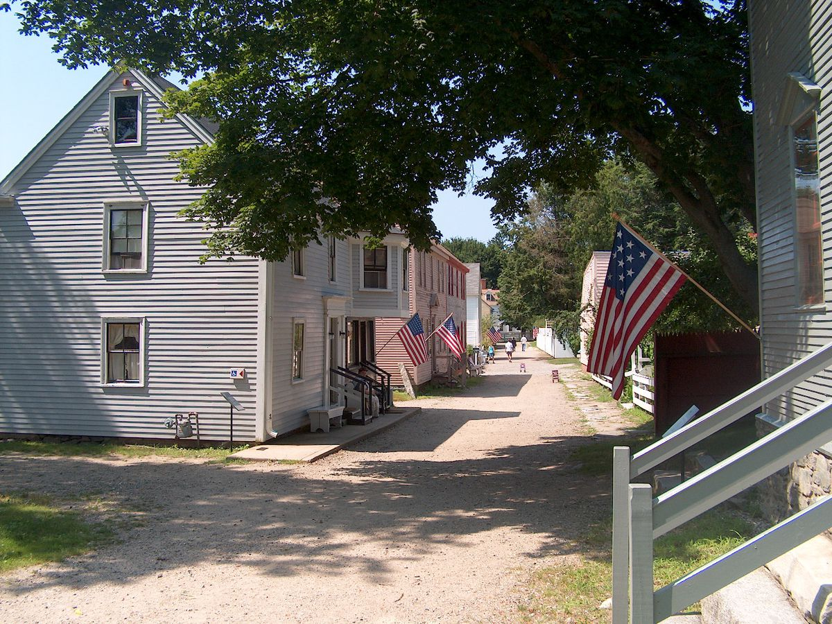 A row of grey houses with flagpoles attached to the exteriors. There are United States flags attached to the flagpoles.