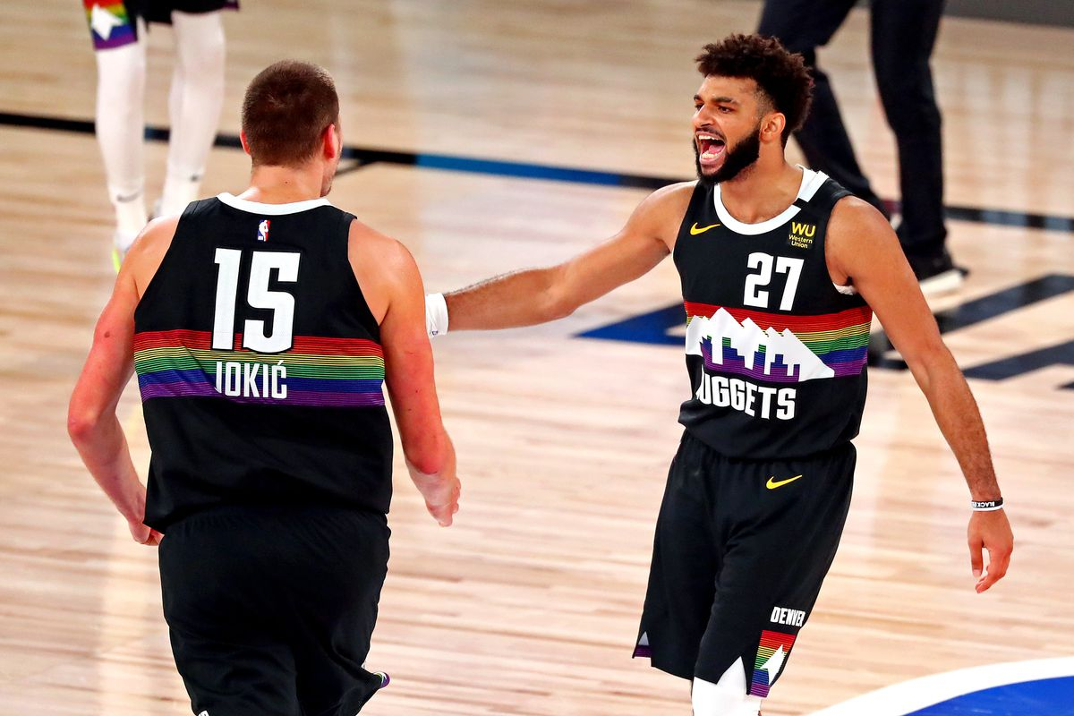 Denver Nuggets guard Jamal Murray reacts with center Nikola Jokic during the fourth quarter against the LA Clippers in game six of the second round of the 2020 NBA Playoffs at ESPN Wide World of Sports Complex.