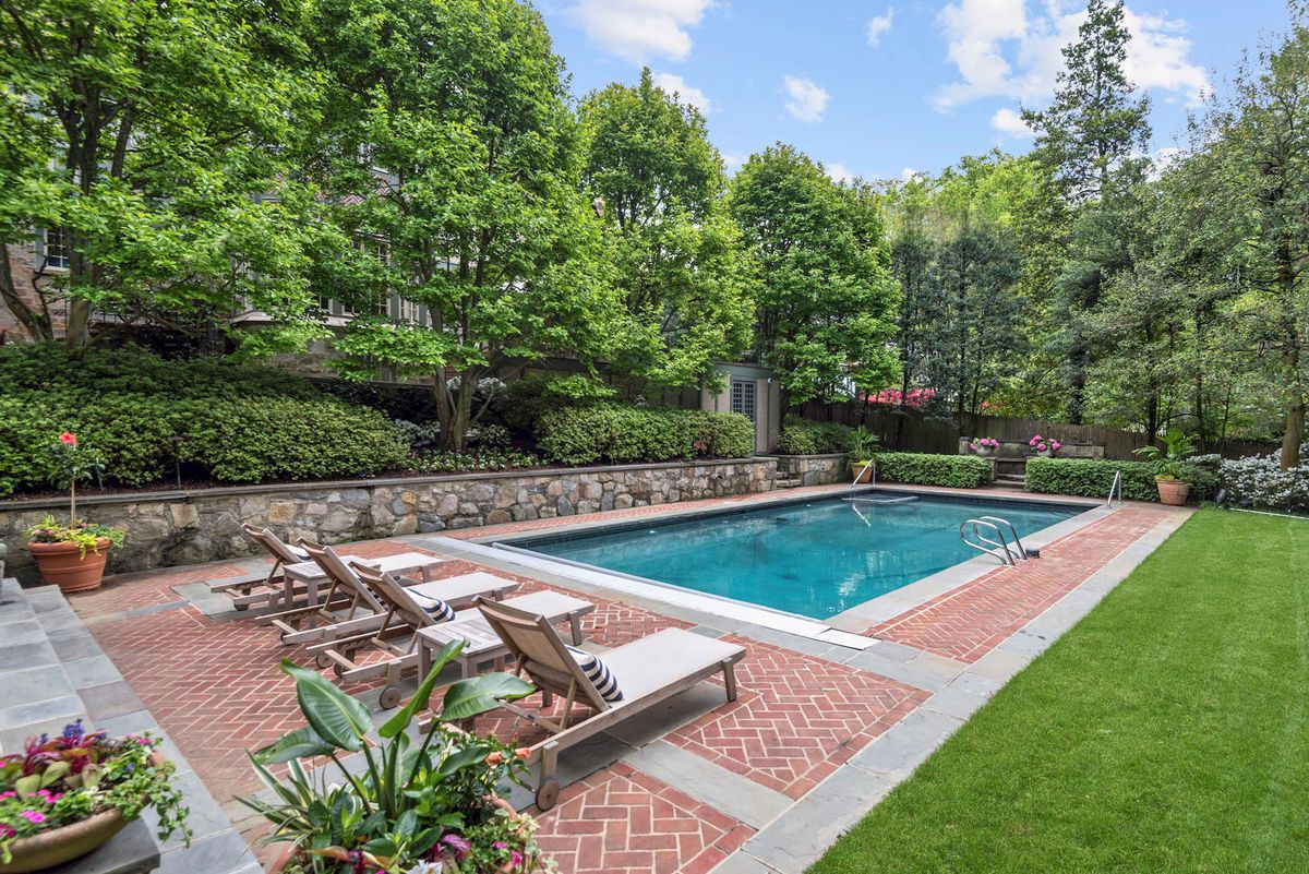 A pool sits surrounded by a brick patio, green grass, and trees.