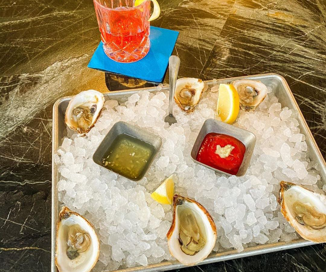a dozen raw oysters on ice and a bright red sazerac cocktail