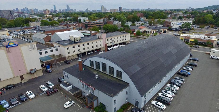 Aerial shot of a long building surrounded by parking, and the roof of the building is barrel-shaped.