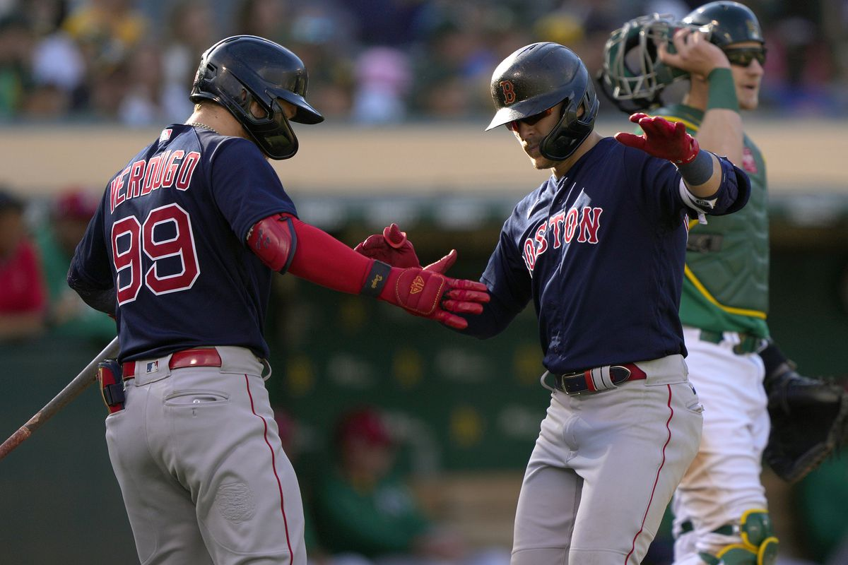 Enrique Hernandez #5 of the Boston Red Sox is congratulated by Alex Verdugo #99 after Hernandez hit a solo home run against the Oakland Athletics in the top of the seventh inning at RingCentral Coliseum on July 03, 2021 in Oakland, California.