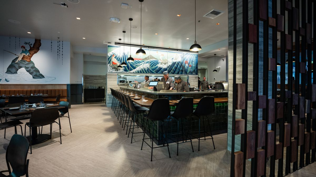 A look at Bamboo Sushi's interior, with soft lighting, colorful murals in the background, and sushi chefs working behind a bar.