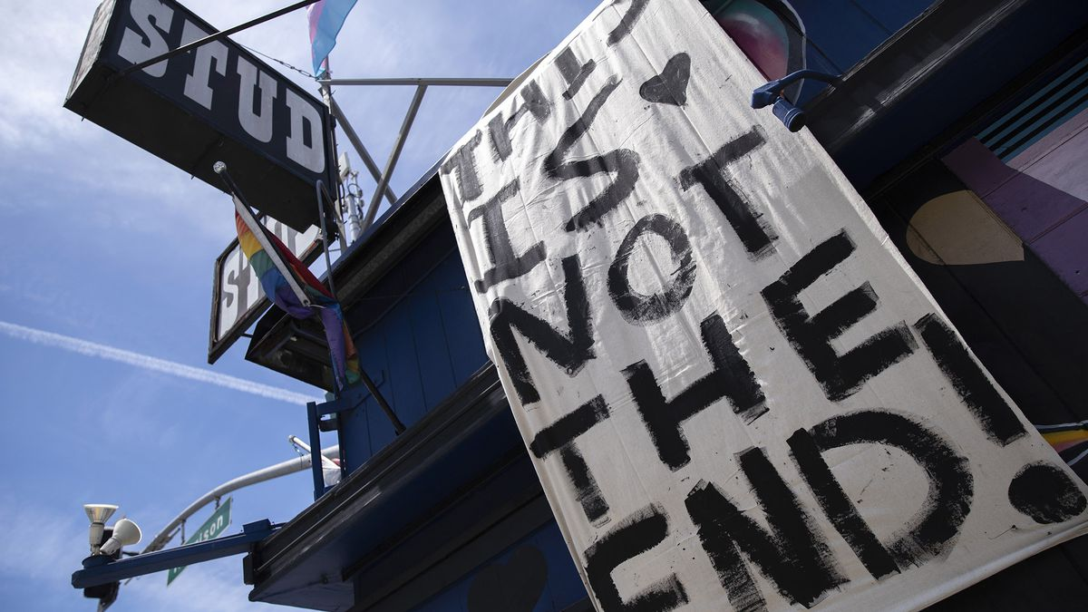 """A hand painted sign with black paint on a white sheet hangs down the side of a multi-story building. The sign reads, """"This is not the end"""". The building has rainbow pride flags and a large old sign that says STUD."""