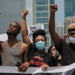 William Hooks, 24, from Englewood, Bianca Jones, 34, from Roseland, and Eric Hooks, 19, from Lawndale raise their fists while singing during a march that commemorates Juneteenth on June 19, 2020