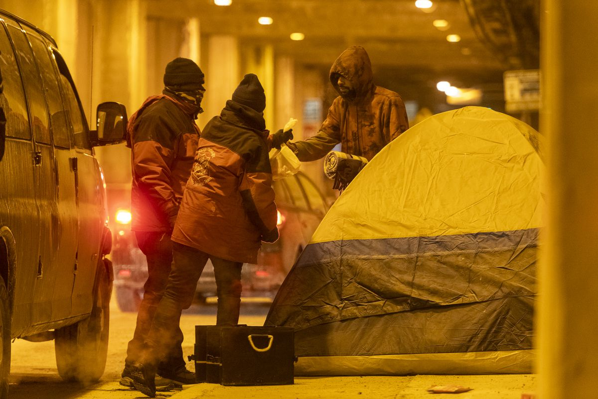 Members of The Salvation Army Chicago give a homeless man some supplies, including blankets and hand warmers, down on Lower Wacker Drive.