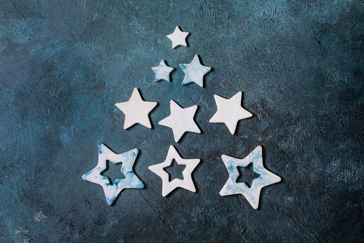 Christmas decoration ceramic stars white and blue glazed. different size. as christmas tree shape over blue texture background. Christmas and New year greeting card. Flat lay. space.