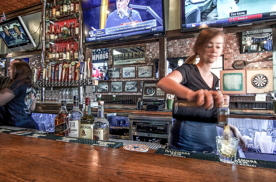 A server pours a drink at an Irish bar as TVs play in the background.