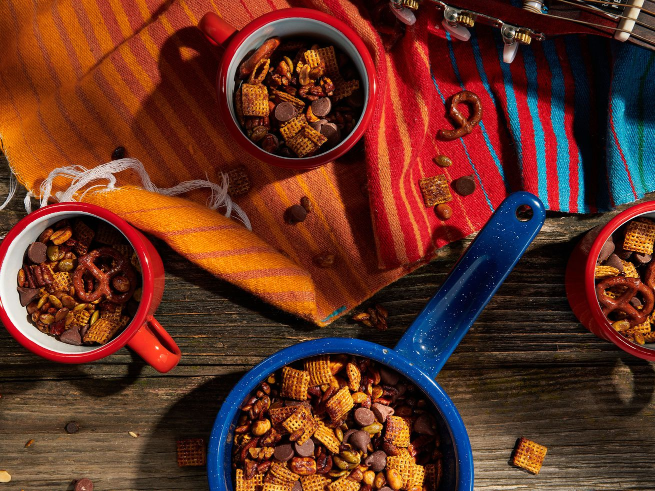 Tin camping cups filled with trail mix as seen from above on a picnic table, with colorful napkins alongside.