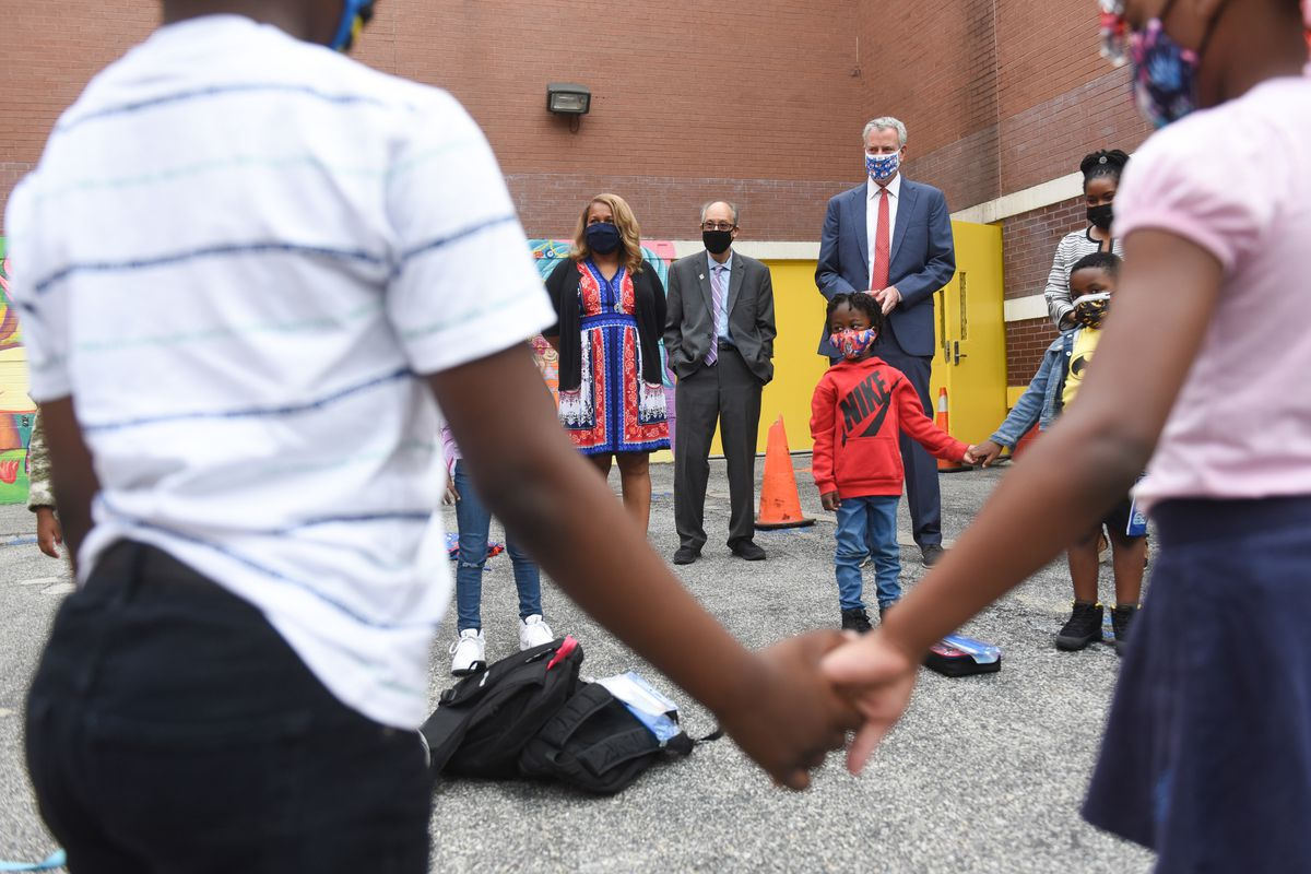 Two students holding hands in the foreground, while in the back stand Mayor Bill de Blasio and Schools Chancellor Meisha Porter.