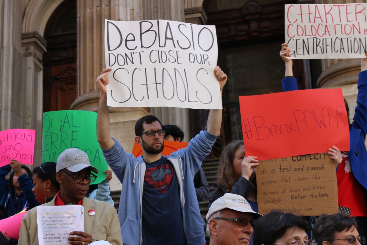 Protesters gathered at the education department's headquarters to protest a previous set of closure plans.
