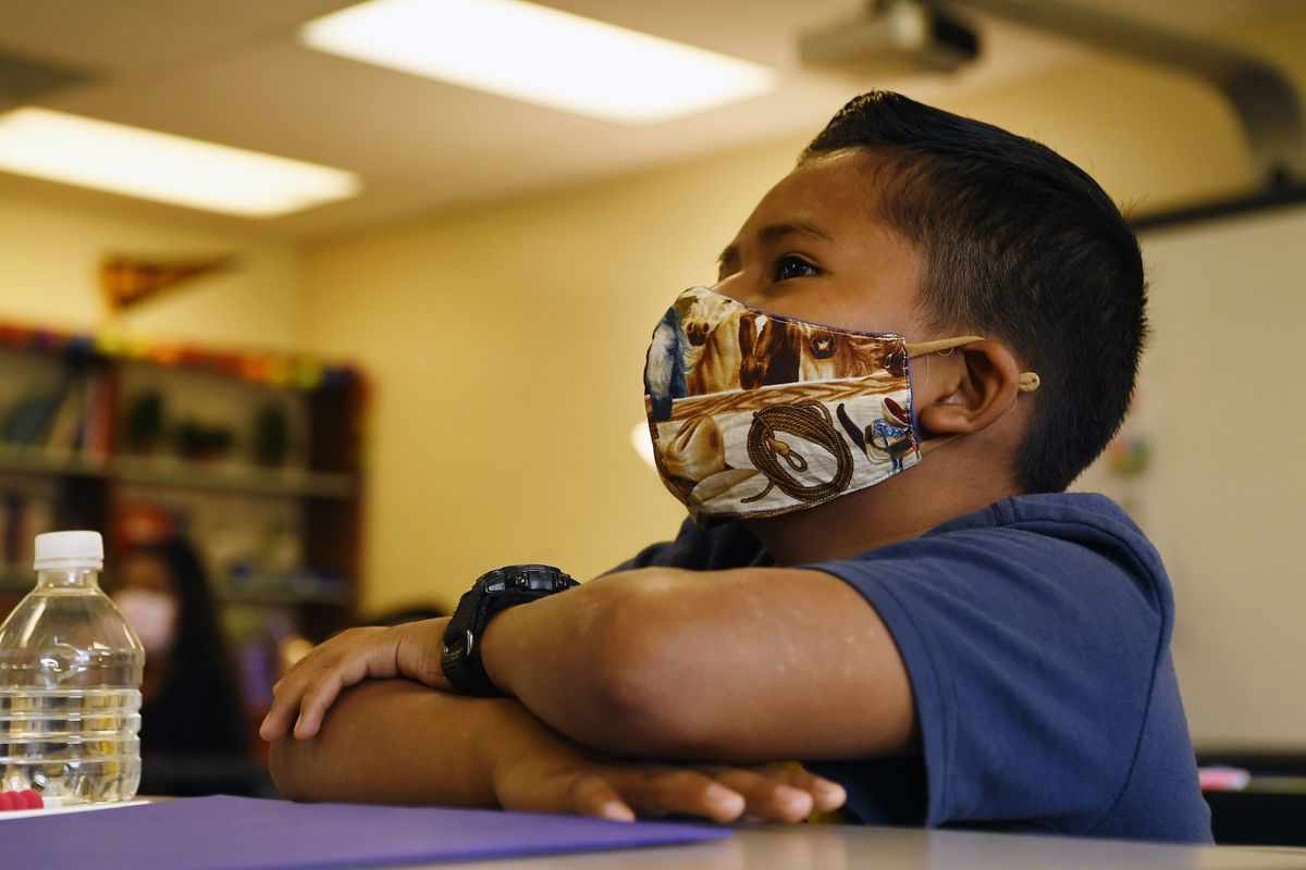 Young boy wearing a mask sits at a desk.